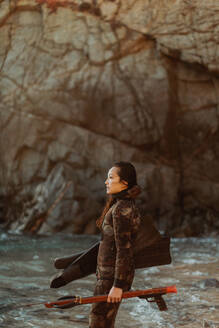 Woman with flippers and speargun on beach, Big Sur, California, United States - ISF22312