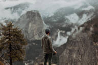 Hiker enjoying view of fog covering valley, Yosemite National Park, California, United States - ISF22315