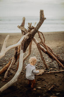 Toddler playing beside wickiup on beach - ISF22354
