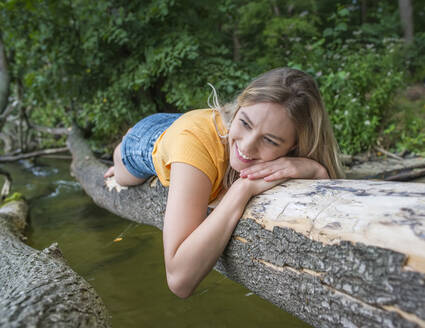 Smiling woman laying on a tree trunk at lakeshore - BFRF02108