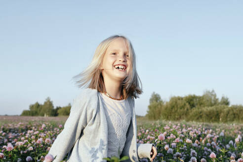 Portrait of a smiling girl standing on a clover field - EYAF00618