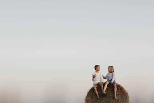 Two kids sitting on the haystack - EYAF00627
