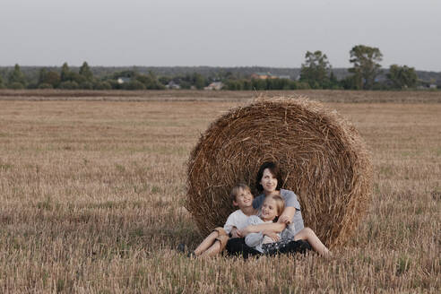 Woman with two kids sitting near a haystack on a stubble field - EYAF00630