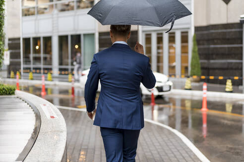 Rear view of young businessman with umbrella during a rainy day in Bangkok - MAUF02979