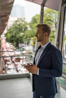 Young businessman on pedestrian bridge - MAUF02991