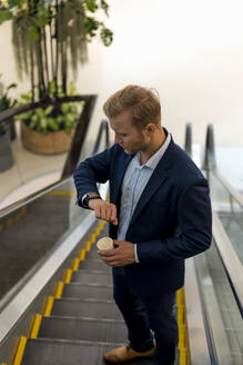 Young businessman with a coffee to go checking the time on escalator - MAUF03000