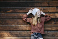 Smiling girl standing in front of a wooden wall outdoors - HMEF00653