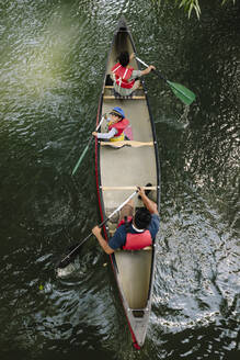 Overhead view of father canoeing with two sons on lake - HEROF39250