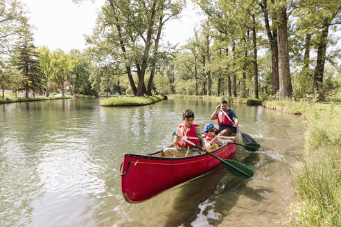 Father canoeing with two sons on lake in park - HEROF39253