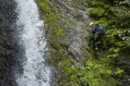 Side view of man rappelling beside waterfall in Canyon. - CAVF65767