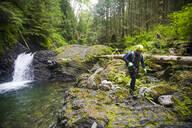 Hiker walks over rocky terrain beside waterfall in dense forest. - CAVF65773