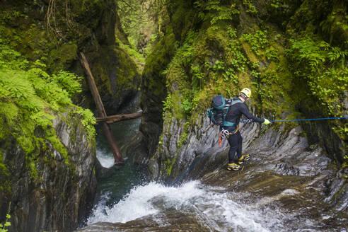 Man rappelling beside waterfall in Frost Creek Canyon. - CAVF65776