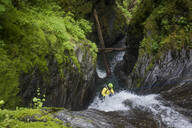 High angle view of man rappelling down a waterfall. - CAVF65782