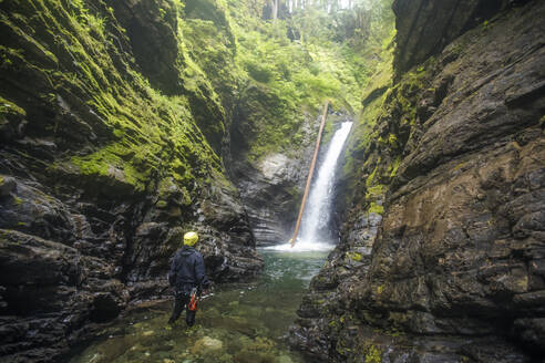 Hiker looks up at large waterfall in Frost Creek Canyon. - CAVF65791