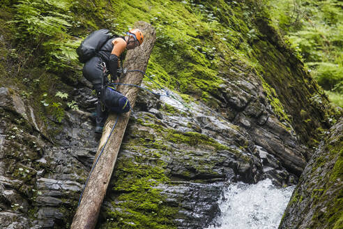 Man carefully moves across log before rappelling into a canyon. - CAVF65794