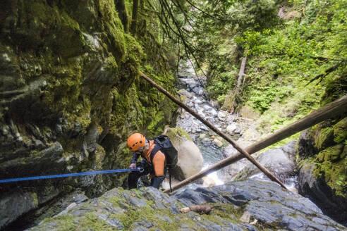 Man rappelling beside waterfall in Frost Creek Canyon. - CAVF65800