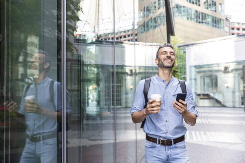 Smiling businessman holding cup of coffee and smartphone in the city, Berlin, Germany - WPEF02067