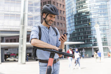 Smiling businessman looking at the smartphone commuting on electric scooter in the city, Berlin, Germany - WPEF02091