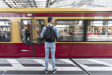 Rear view of man with backpack at the station platform while train coming in - WPEF02097