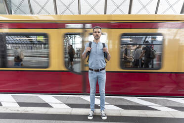 Portrait of man at the station platform with train in background - WPEF02100