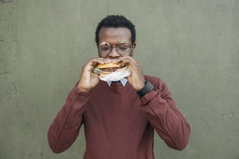 Young man eating cheeseburger, with eyes closed - VPIF01634