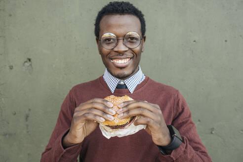 Young man eating cheeseburger, smiling - VPIF01637