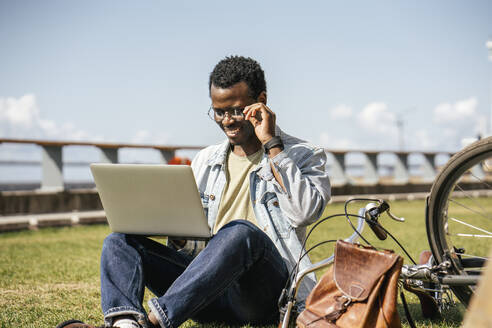 Young man sitting on grass, using laptop - VPIF01697