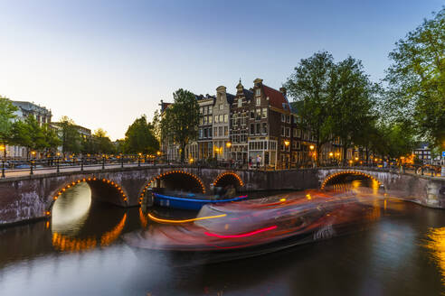 Keizergracht Canal at dusk, trailing light blur from a tourist boat, Amsterdam, North Holland, The Netherlands, Europe - RHPLF12323