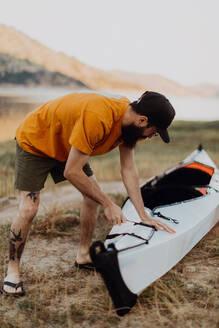 Man preparing kayak by lake, Kaweah, California, United States - ISF22575