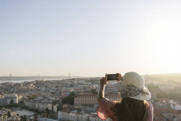 Woman taking a smartphone picture of the city panorama, Lisbon, Portugal - AHSF01006