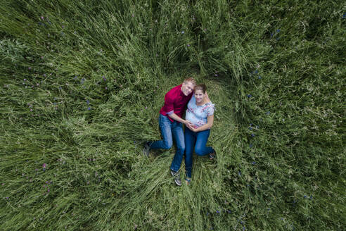 Pregnant woman and man holding baby belly, lying on meadow - HMEF00662