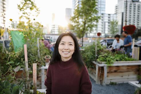 Portrait happy woman in urban community garden - HEROF39303