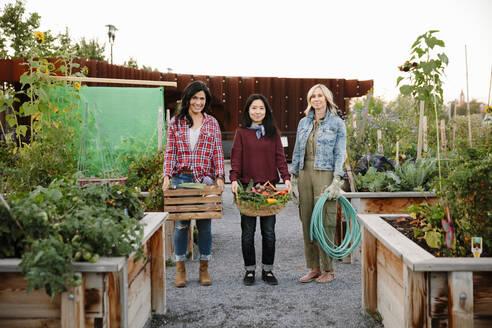 Portrait confident women friends with fresh harvested vegetables in community garden - HEROF39318