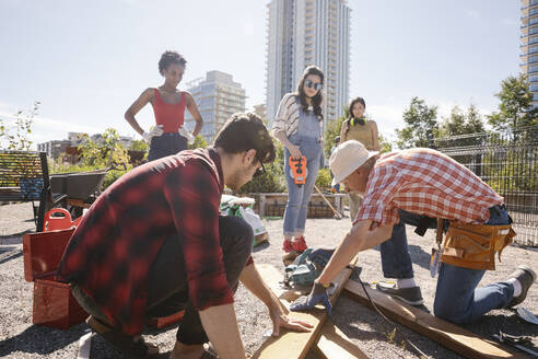 Man guiding young adults building planter box in sunny community garden - HEROF39390