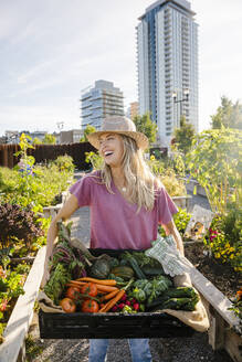 Portrait happy, laughing young woman carrying fresh harvested vegetables in sunny, urban community garden - HEROF39447