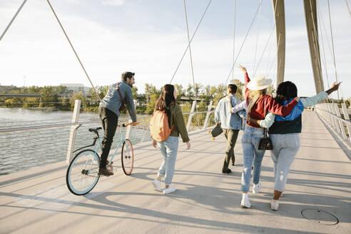 Playful young adult friends on sunny, urban footbridge - HEROF39471