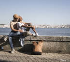 Young couple sitting on a wall at the waterfront, Lisbon, Portugal - UUF19064