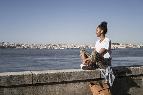 Young woman sitting on a wall at the waterfront, Lisbon, Portugal - UUF19067