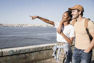 Young couple walking at the waterfront, Lisbon, Portugal - UUF19079