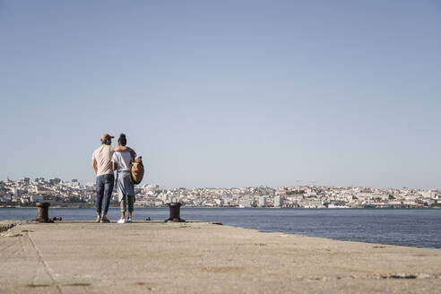 Young couple standing on pier at the waterfront, Lisbon, Portugal - UUF19085