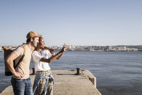 Happy young couple taking a selfie on pier at the waterfront, Lisbon, Portugal - UUF19103