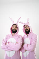 Two male friends with rabbit costumes in front of white background - AFVF04147