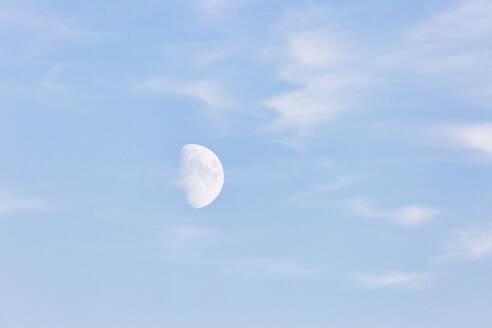 Germany, Brandenburg, Linum, Daytime moon against pastel blue sky - JUBF00357