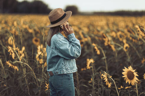 Young girl with blue denim jacket and hat calling in a field of sunflowers in the evening - OCAF00426