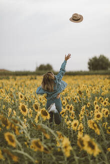 Rear View of young woman with blue denim jacket throwing a hat in a field of sunflowers - OCAF00432
