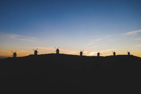 Spain, Province of Toledo, Consuegra, Silhouettes of windmills standing on top of hill at dawn - WPEF02115