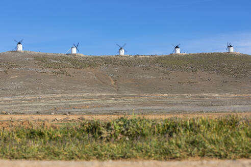 Spain, Province of Toledo, Consuegra, Row of old windmills standing on top of hill - WPEF02130