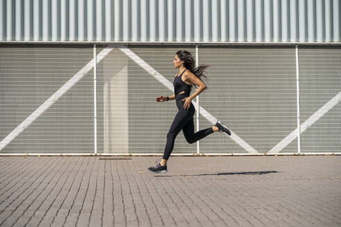 Young female jogger running in front of a wall - MTBF00036