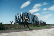 Young woman jogging on a way, modern building in the background - MTBF00039