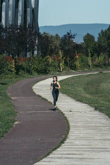Young woman jogging in a park along a red and white way - MTBF00042